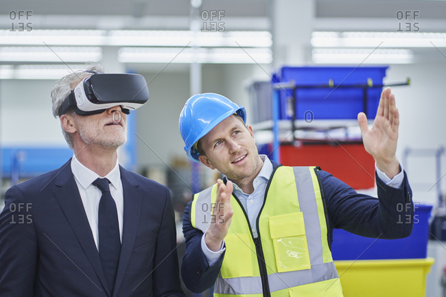 Male supervisor explaining plan to manager wearing VR glasses in factory