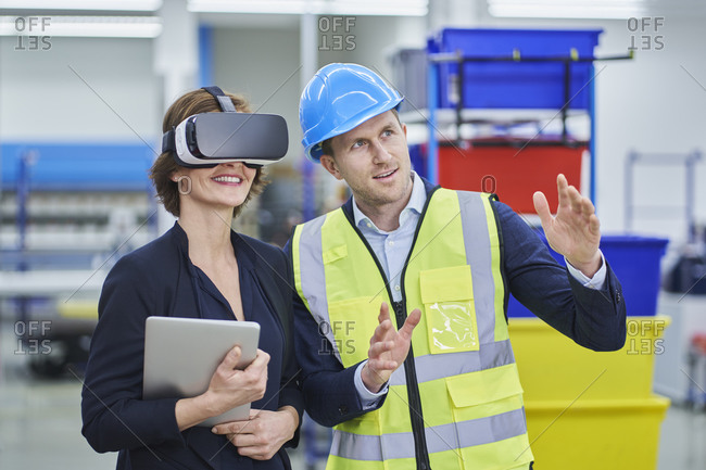 Supervisor explaining plan to female manager wearing VR glasses while holding digital tablet in factory