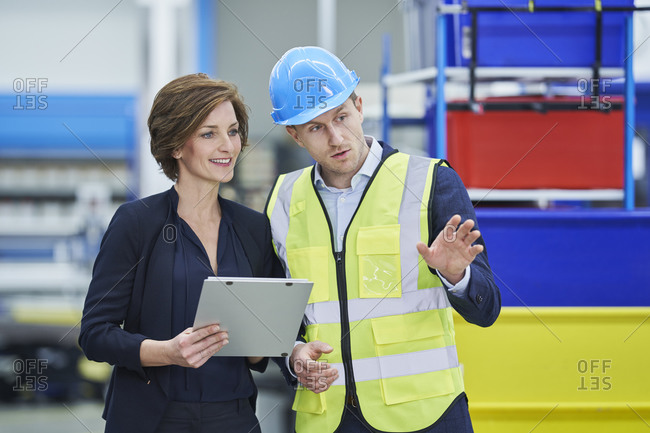 Supervisor explaining plan to female manager holding clipboard in factory