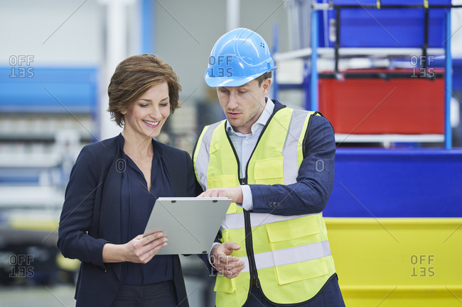 Supervisor explaining plan to happy female manager on clipboard in factory