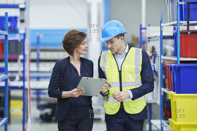 Supervisor and female manager discussing over clipboard in factory