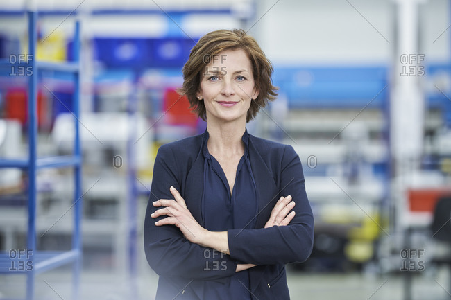 Confident female manager standing arms crossed in factory