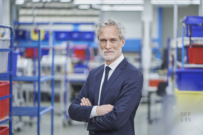 Confident male manager standing arms crossed in factory