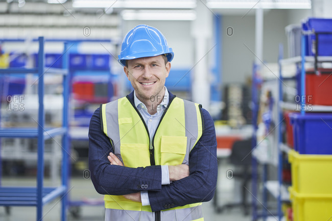 Confident male supervisor in hardhat and reflective clothing standing arms crossed at factory