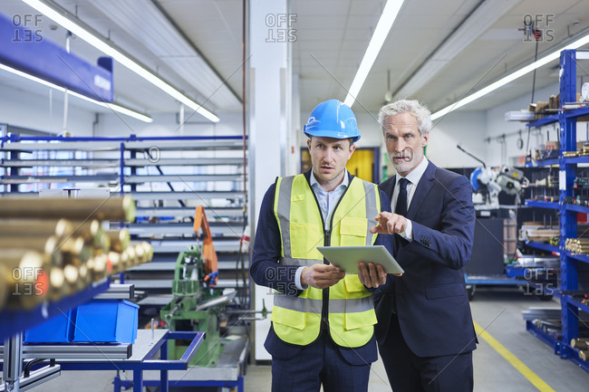 Supervisor and male manager discussing over digital tablet in factory