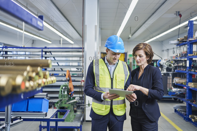 Female manager discussing over digital tablet with male supervisor in industry
