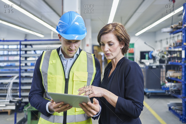 Female manager discussing over digital tablet with male supervisor in factory