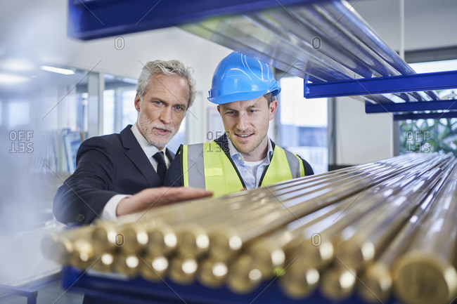 Manager discussing over metallic pipes with supervisor in factory