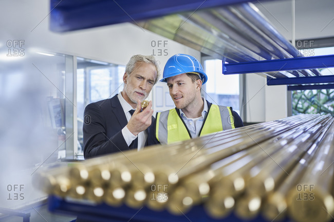 Manager discussing over metallic bolt with supervisor in factory