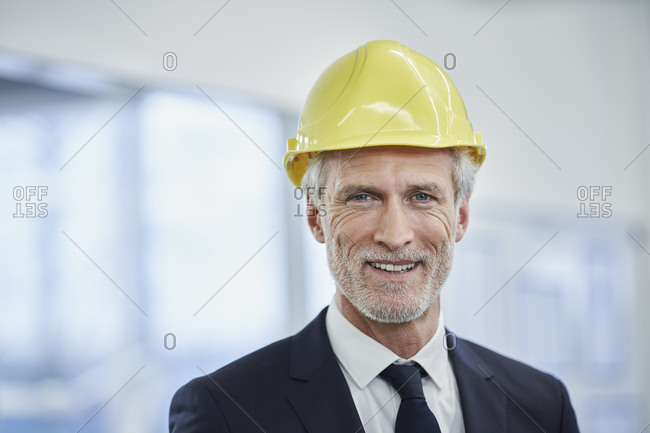 Happy mature male manager wearing yellow hardhat in factory