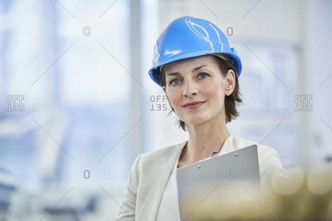 Confident female manager wearing blue hardhat in factory