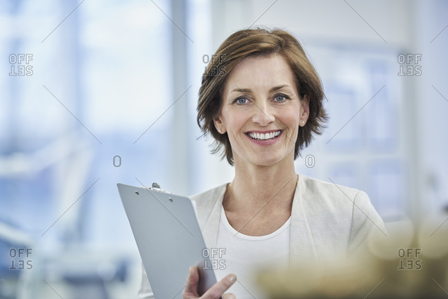 Happy female manager holding clipboard in factory