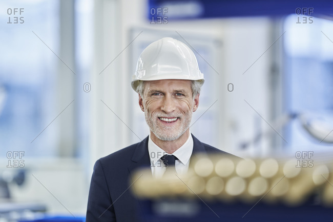 Happy mature male manager wearing white hardhat in factory