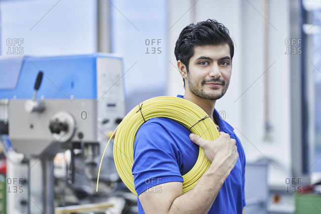 Confident male worker carrying rolled up cables in factory