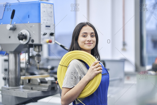 Happy female worker carrying rolled up cables in factory