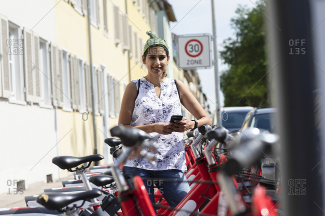 Smiling woman holding smart phone while standing by rental bicycles in city
