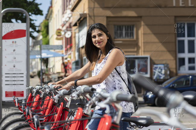 Happy mid adult woman standing amidst rental bicycles in city