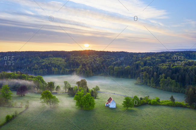 Germany- Bavaria- Egling- Drone view of Kapelle Saint Koloman at foggy springtime sunrise