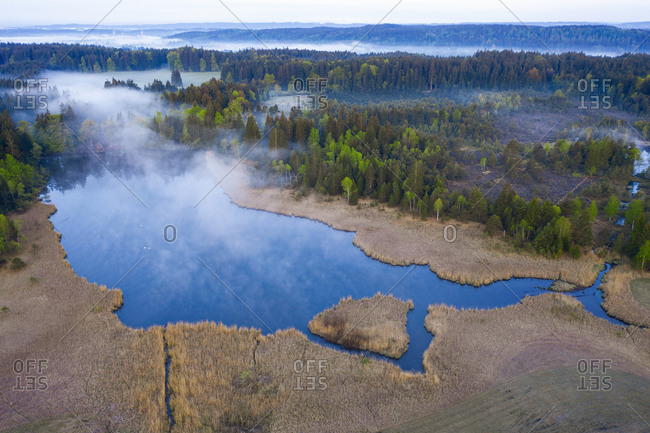 Germany- Bavaria- Egling- Drone view of Mooshamer Weiher lake at foggy dawn