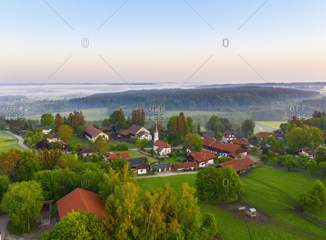 Germany- Bavaria- Walchstadt- Drone view of countryside village at foggy sunrise