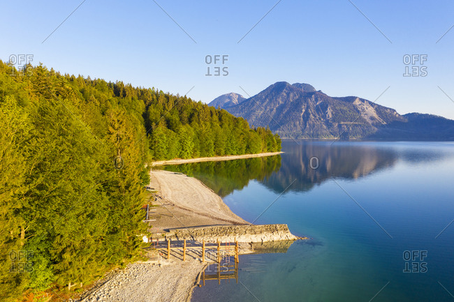 Germany- Bavaria- Kochel am See- Drone view of forested shore of Lake Walchen in spring