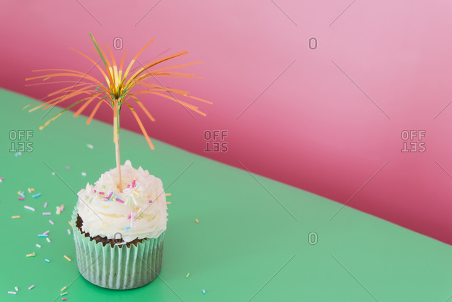 Single cupcake decorated with sugar sprinkles and party confetti