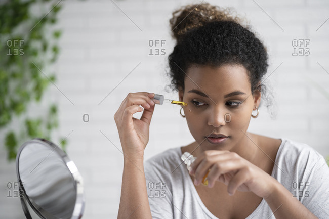Close-up of young woman applying serum with pipette while looking in mirror at home