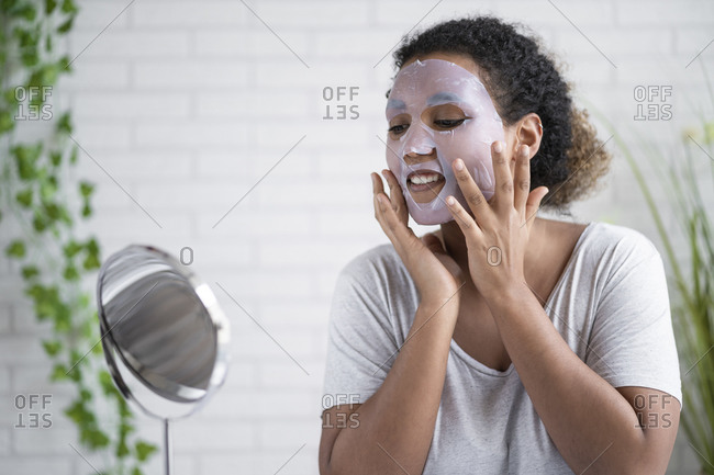 Young woman applying paper facial mask while looking in mirror at home