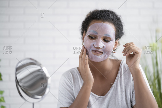 Woman applying paper facial mask while looking in mirror at home
