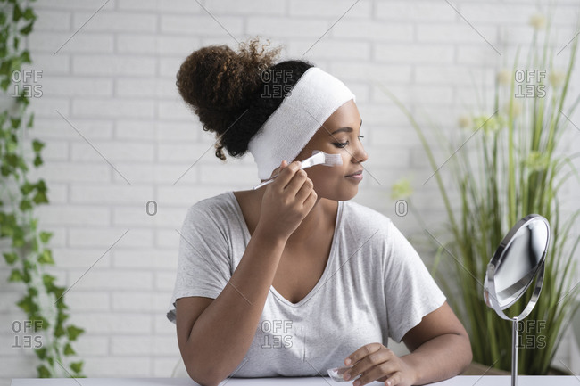 Young woman wearing headband applying facial mask while looking in mirror at home