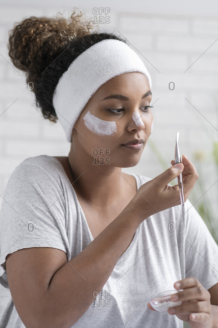 Close-up of young woman wearing headband applying facial mask with brush at home