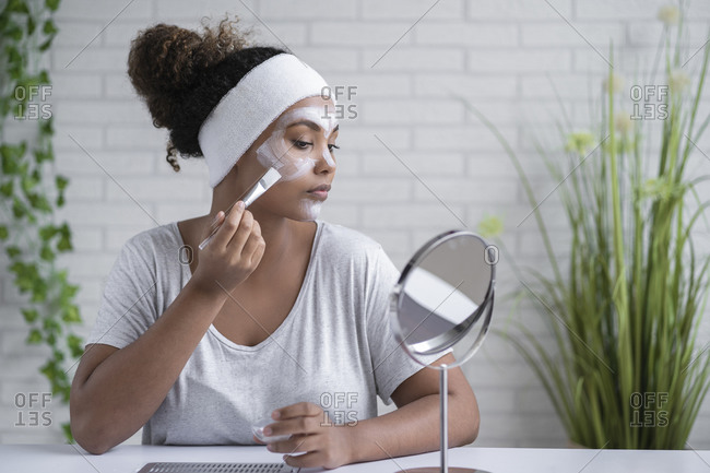 Woman wearing headband applying facial mask while looking in mirror at home