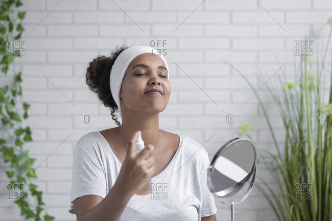 Young woman with eyes closed spraying facial mist at home