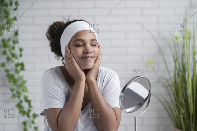 Woman with eyes closed applying cleansing foam on face at home