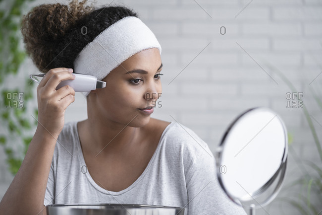 Close-up of young woman applying ultrasonic peel while looking in mirror