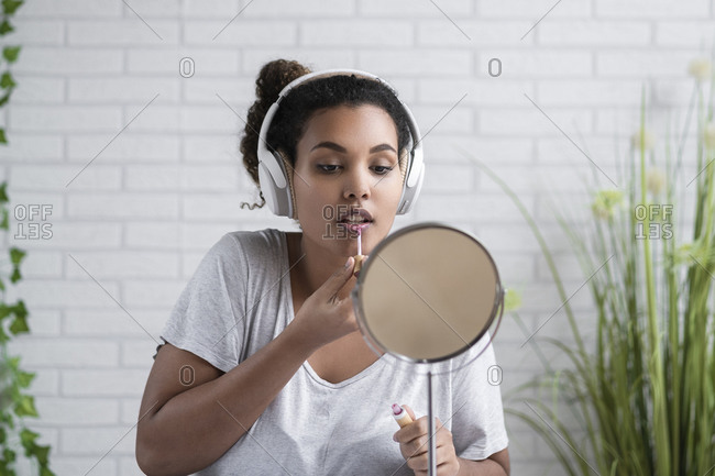Young woman listening music through headphones applying lip gloss at home