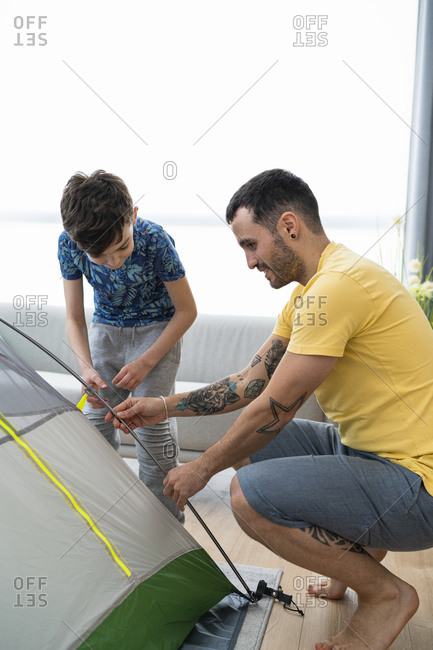 Father and son putting up tent at home
