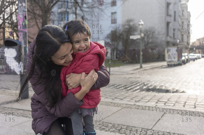 Happy woman embracing her daughter while kneeling on footpath in city