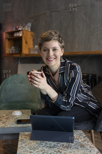 Portrait of smiling freelancer sitting in a coffee shop with digital tablet and smartphone