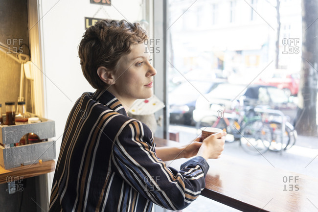 Pensive freelancer in a coffee shop looking out of window