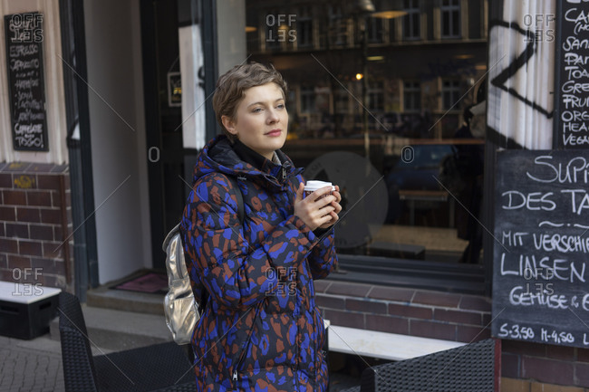 Portrait of daydreaming woman with backpack and coffee to go in front of a coffee shop