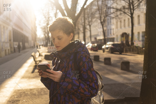 Portrait of woman with backpack and coffee to go looking at cell phone in the evening- Berlin- Germany