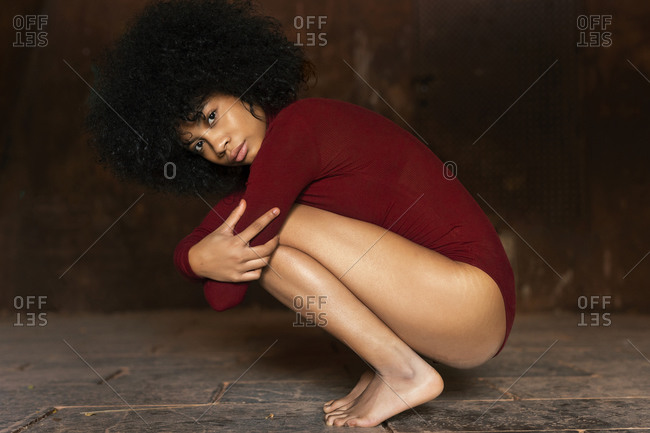 Young woman in red bodysuit- crouching- hugging knees