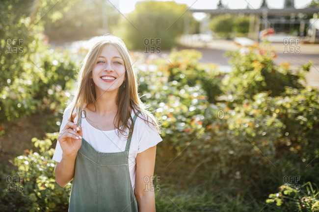 Portrait of smiling young woman in public garden at backlight