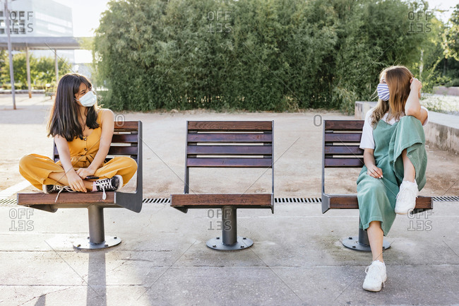 Two friends wearing protective masks meeting outdoors during Corona crisis and keeping distance