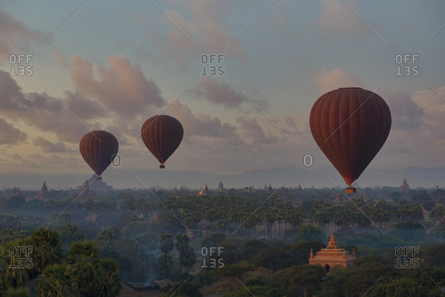 Myanmar- Mandalay Region- Bagan- Hot air balloons flying over Buddhist temples at dawn
