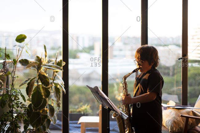 Boy exercising to play the saxophone at home in the evening