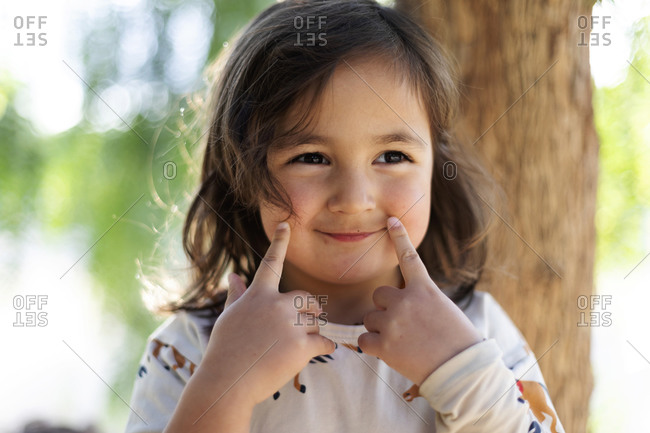 Portrait of smiling little girl with fingers on her face