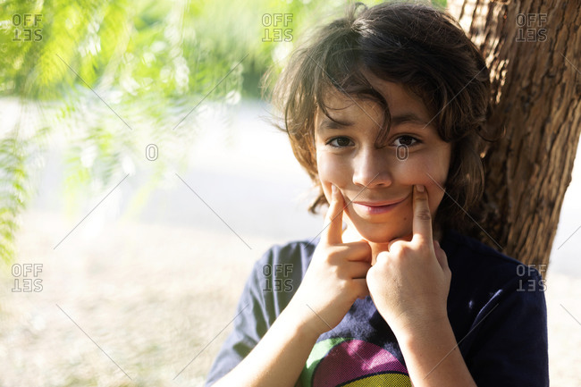 Portrait of boy pulling corner of mouth with his fingers