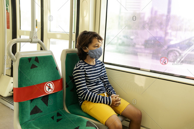 Boy wearing protective mask in tramway
